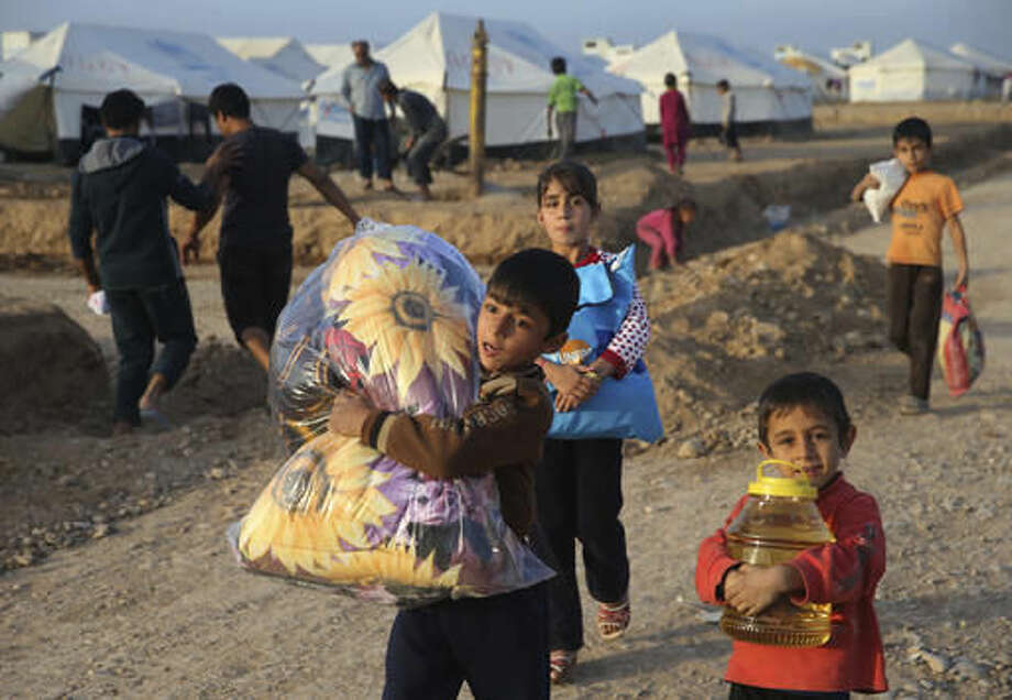 Displaced Iraqi boys, who fled from Mosul with their families, carry food and other aid supplies at a camp for internally displaced people in Hassan Sham, east of Mosul, Iraq, Saturday, Nov. 12, 2016. The urban landscape inside Mosul proper makes defense easier for the Islamic State group, eager to hold on to the last major Iraqi stronghold of their self-styled caliphate. (AP Photo/Hussein Malla) Photo: Hussein Malla