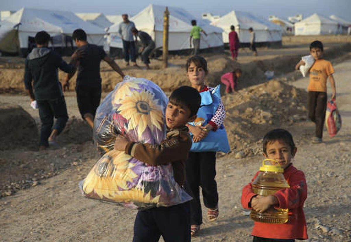 Displaced Iraqi boys, who fled from Mosul with their families, carry food and other aid supplies at a camp for internally displaced people in Hassan Sham, east of Mosul, Iraq, Saturday, Nov. 12, 2016. The urban landscape inside Mosul proper makes defense easier for the Islamic State group, eager to hold on to the last major Iraqi stronghold of their self-styled caliphate. (AP Photo/Hussein Malla)