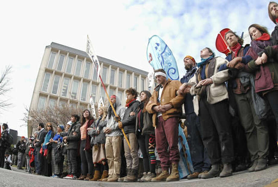 Dakota Pipeline protesters stand arm-in-arm at the intersection of Rosser Avenue and Fourth Street in downtown Bismarck, N.D., after marching from the state Capitol to the William L. Guy Federal Building, Monday, Nov. 14, 2016. (Mike McCleary/The Bismarck Tribune via AP) Photo: Mike McCleary