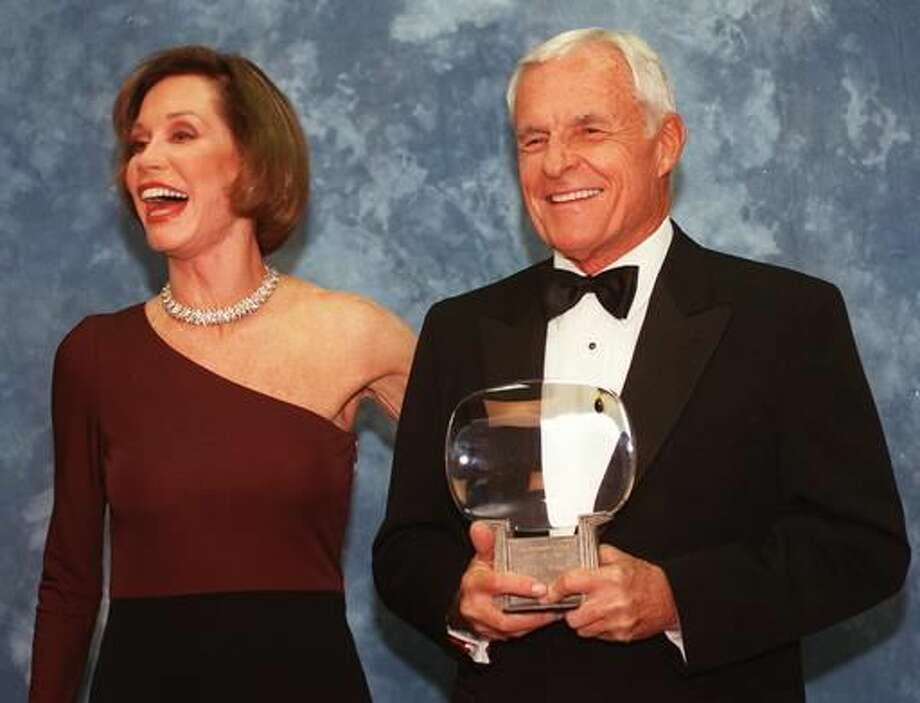 "FILE - In this Saturday, Nov. 1, 1997, file photo, Television executive Grant Tinker holds up his Hall of Fame award alongside his ex-wife Mary Tyler Moore at the Academy of Television Arts & Sciences' 13th Annual Hall of Fame induction ceremonies in the North Hollywood section of Los Angeles. Tinker, who brought ""The Mary Tyler Moore Show"" and other hits to the screen as a producer and a network boss, has died. Tinker died Monday, Nov. 28, 2016, at his home in Los Angeles, according to his son, Mark Tinker. (AP Photo/Chris Pizzello, File) Photo: Chris Pizzello"