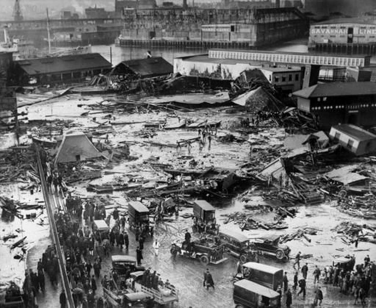 FILE - In this Jan. 15, 1919, file photo, the ruins of tanks containing 2 1/2 million gallons of molasses lie in a heap after an eruption that hurled trucks against buildings and crumpled houses in the North End of Boston. Harvard University researchers said in November 2016 that they've solved the mystery behind the disaster that killed 21 people, injured 150 others and flattened buildings when a giant storage tank ruptured. The scientists concluded that the comparatively warm molasses thickened rapidly when exposed to the wintry air, trapping victims in hardening goop. (AP Photo, File)