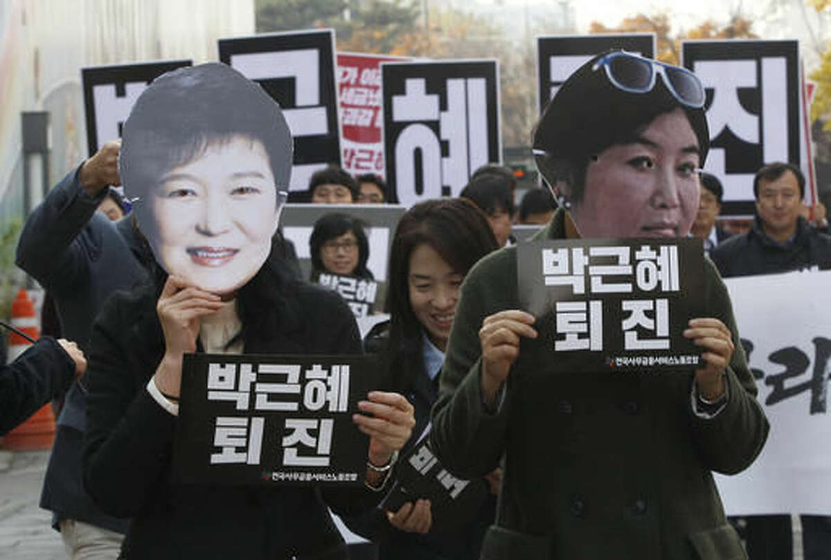 FILE - In this Nov. 18, 2016, file photo, protesters wearing masks of South Korean President Park Geun-hye, left and Choi Soon-sil, Park's longtime friend, in Seoul, South Korea. South Korean prosecutors on Sunday, Nov. 20, 2016, said they believe Park conspired in criminal activities of a secretive confidante who allegedly manipulated government affairs and exploited her presidential ties to amass an illicit fortune - a damning revelation that may convince opposition parties to push for her impeachment. The placards held by the protesters read: