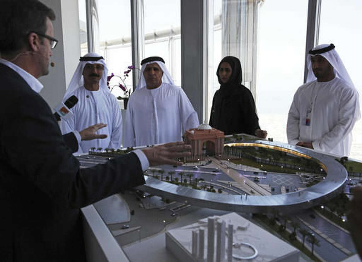 Rob Lloyd, the CEO of Hyperloop One, left, shows a model to Emirati officials including Mattar al-Tayer, the director-general and chairman of Dubai's Roads & Transport Authority, third left, in Dubai, United Arab Emirates, Tuesday, Nov. 8, 2016. The futuristic city-state of Dubai announced a deal on Tuesday with Los Angeles-based Hyperloop One to study the potential for building a line linking it to the Emirati capital of Abu Dhabi. (AP Photo/Jon Gambrell)
