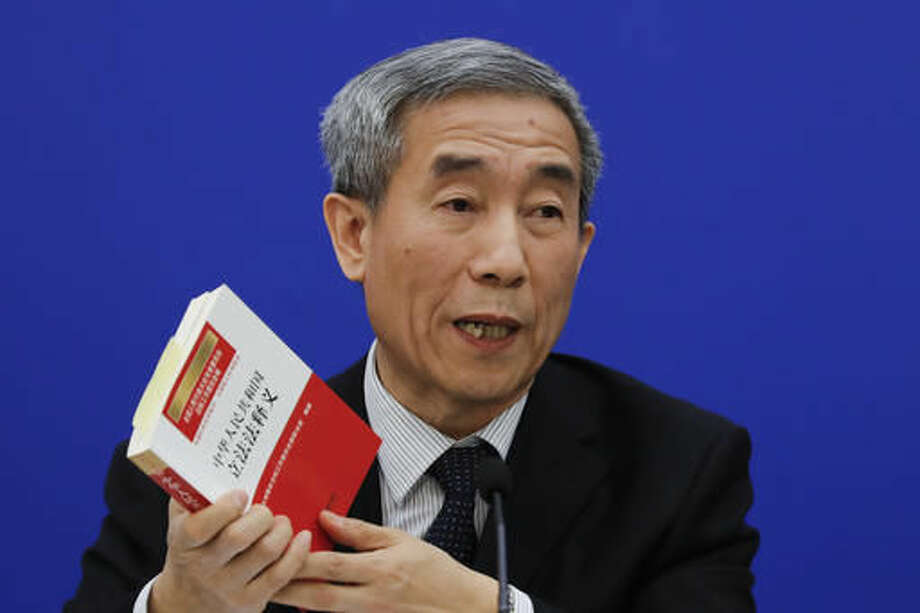 Li Fei, deputy secretary general of the National People's Congress Standing Committee, holds a China's legislation law book while speaking during a press conference at the Great Hall of the People in Beijing, Monday, Nov. 7, 2016. China's top legislature effectively barred two democratically elected separatist lawmakers from taking office in Hong Kong with a ruling Monday on the city's constitution, an intervention into a local political dispute that's likely to spark further turmoil in the southern Chinese city. (AP Photo/Andy Wong) Photo: Andy Wong