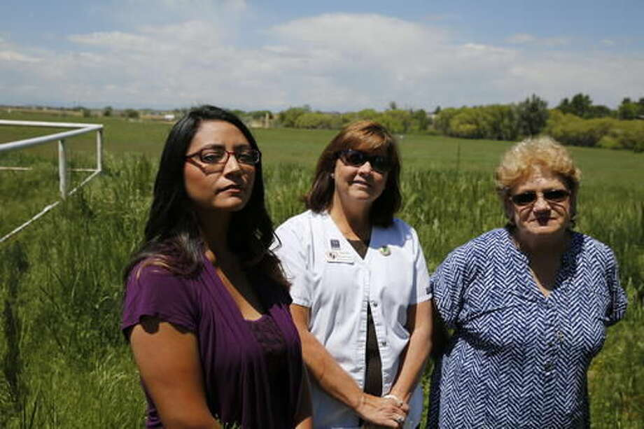 In this May 31, 2016 photo, Nelly Morales, left, Michelle Young, center, and Dawn Stein are photographed on Stein's property, next to a planned oil well complex in Greeley, Colo. Residents of the neighborhood filed a suit against the Colorado Oil and Gas Conservation Commission, alleging the commission didn't enforce rules that would protect residents from some of the impacts of the site. (AP Photo/Brennan Linsley) Photo: Brennan Linsley