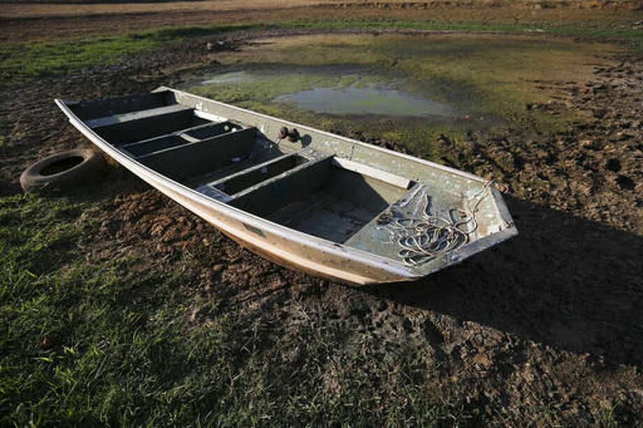 FILE - In this Wednesday, Oct. 26, 2016 file photo, an abandoned boat sits in the remains of a dried out pond in Dawson, Ala. Though water shortages have yet to drastically change most people's lifestyles, southerners are beginning to realize that they'll need to save their drinking supplies with no end in sight to an eight-month drought. Already, watering lawns and washing cars is restricted in some parts of the South, and more severe water limits loom if long-range forecasts of below-normal rain hold true through the rest of 2016. (AP Photo/Brynn Anderson, File) Photo: Brynn Anderson