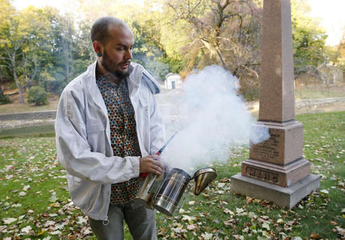 In this Nov. 2, 2016 photo, beekeeper Davin Larson, 30, prepares his bee smoker before inspecting his six honeybee hives at Brooklyn's Green-Wood cemetery, a national historic landmark, in New York. When bees think their hive is under attack, they release an alarm pheromone to alert other bees, agitating the entire hive. Smoke masks these pheromones, allowing the beekeeper to do his hive inspection. During his inspection, Larson will look for intruders and predators and make certain the bees have water nearby. (AP Photo/Kathy Willens)