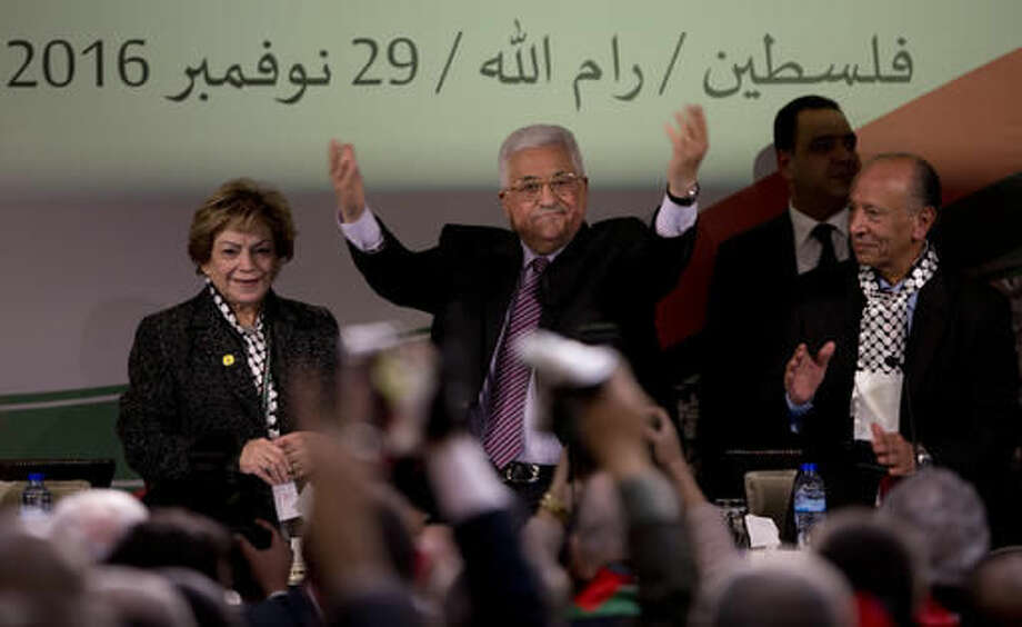 """Palestinian President Mahmoud Abbas, center, is greeted by fellow Fatah members as he arrives during the second day of the Fatah party conference, in the West Bank city of Ramallah, Wednesday, Nov. 30, 2016. Palestinian Fatah movement holds its seventh conference in Ramallah with some fourteen hundred members participating and led by Palestinian President Mahmoud Abbas. The conference is to elect the party's two main decision making bodies. Arabic reads """" Palestine, Ramallah, November 29, 2016."""" (AP Photo/Majdi Mohammed) Photo: Majdi Mohammed"""