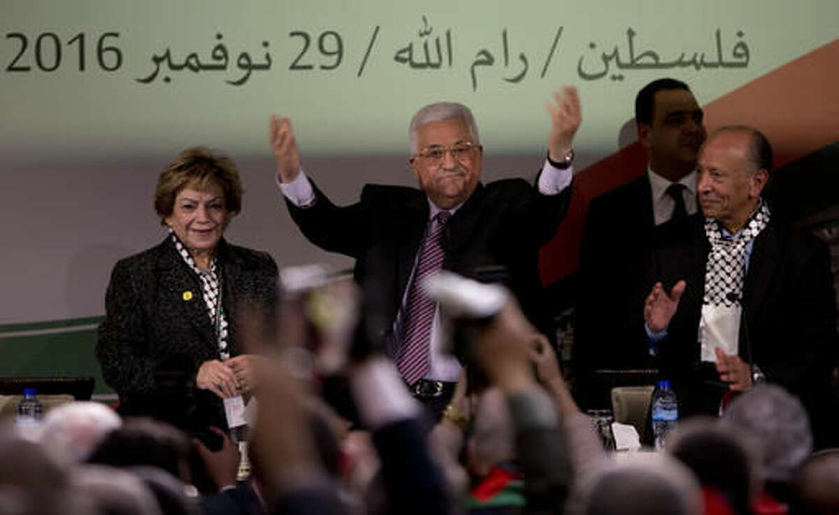 """Palestinian President Mahmoud Abbas, center, is greeted by fellow Fatah members as he arrives during the second day of the Fatah party conference, in the West Bank city of Ramallah, Wednesday, Nov. 30, 2016. Palestinian Fatah movement holds its seventh conference in Ramallah with some fourteen hundred members participating and led by Palestinian President Mahmoud Abbas. The conference is to elect the party's two main decision making bodies. Arabic reads """" Palestine, Ramallah, November 29, 2016."""" (AP Photo/Majdi Mohammed)"""