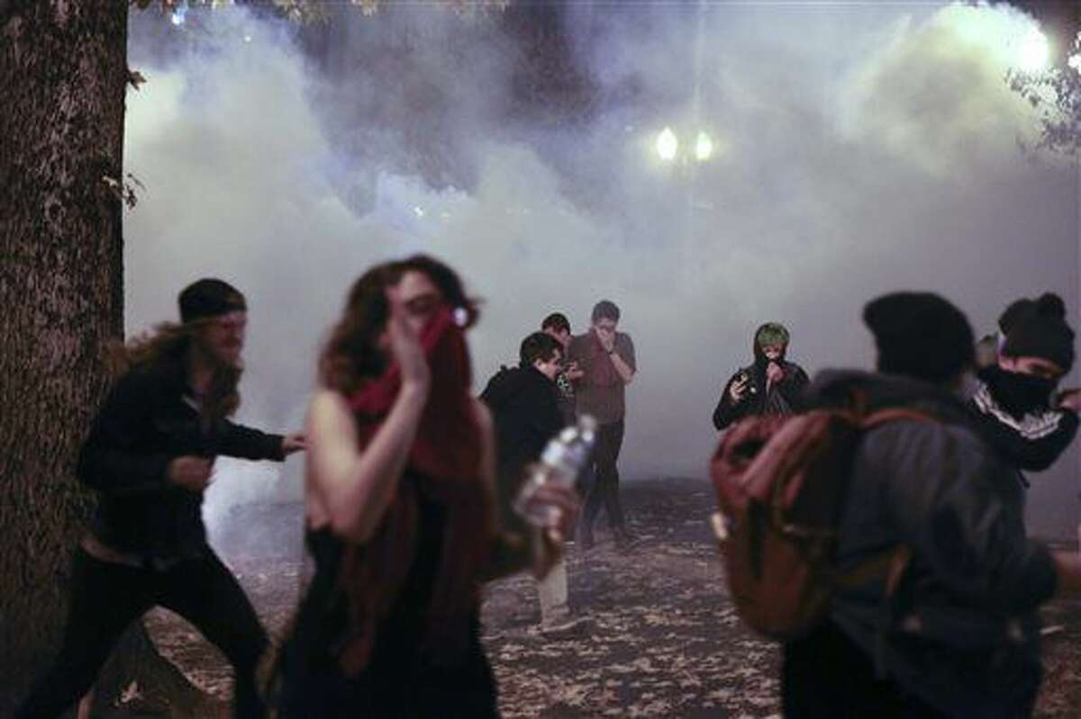 """Police in downtown Portland, Ore., attempt to disperse people protesting the election of President-elect, Donald Trump, Friday, Nov. 11, 2016. In Portland, police used tear gas and flash-bang grenades Friday to try to disperse the crowd after hundreds of people marched through the city, disrupting traffic and spray-painting graffiti. Authorities said """"burning projectiles"""" were thrown at police and vandalism and assault had taken place during the rally, which organizers had billed as peaceful earlier in the day. (Stephanie Yao Long/The Oregonian via AP)"""