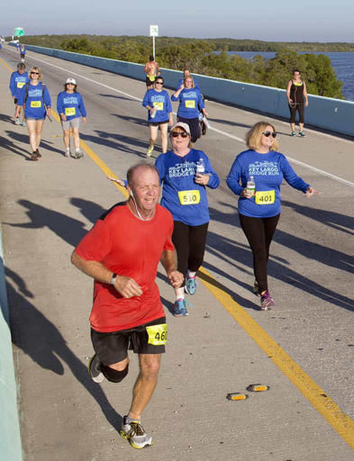 In this photo provided by the Florida Keys News Bureau, competitors in the 5k division of the Key Largo Bridge Run head to the finish line Saturday, Nov. 12, 2016. Some 465 registered entrants competed in 5k, 10k and half-marathon classes that took participants out and back over the 1.4-mile-long Jewfish Creek Bridge and land areas. (Bob Care/Florida Keys News Bureau via AP )