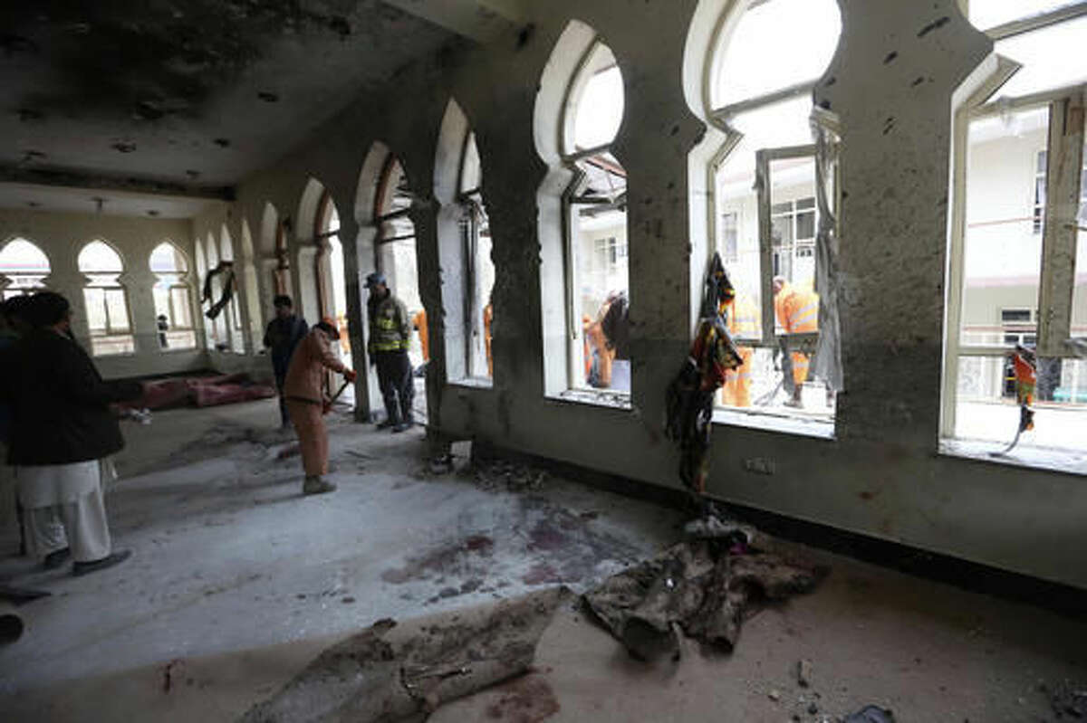 Afghan Municipality workers sweep Baqir-ul Ulom mosque after a suicide attack, in Kabul, Afghanistan, Monday, Nov. 21, 2016. An Afghan official says that dozens of civilians have been killed after a suicide bomber attacked a Shiite mosque in the capital. (AP Photo/Rahmat Gul)