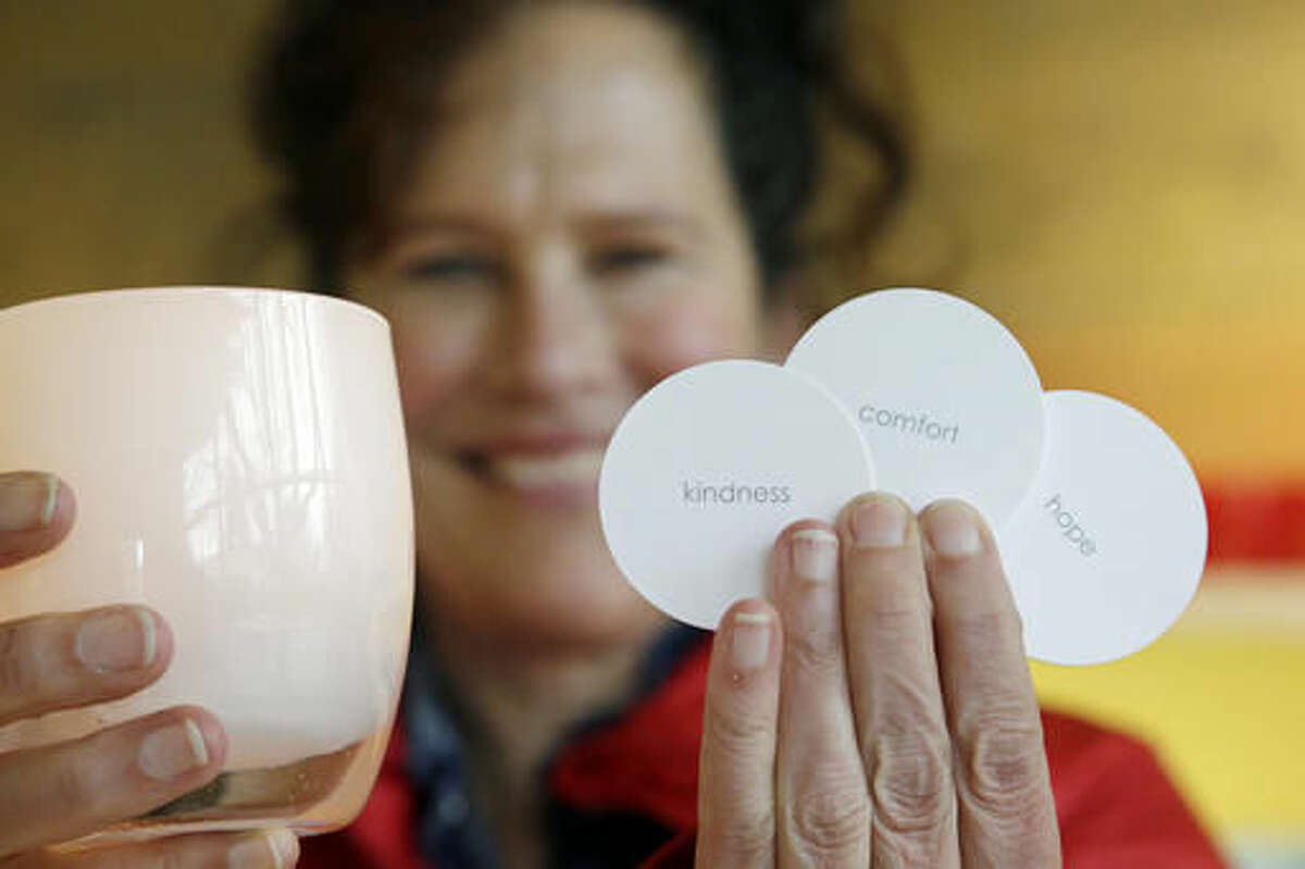 In this Tuesday, Nov. 22, 2016, photo, Lee Rhodes, owner of Glassybaby, holds one of her votive candle holders and several cards used for individual descriptions of each holder made there, including