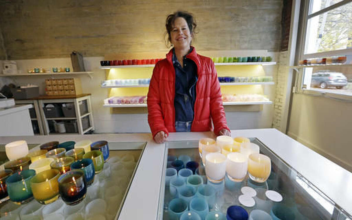 In this Tuesday, Nov. 22, 2016, photo, Lee Rhodes, owner of Glassybaby, poses for a photo near votive candle holders on display at her shop in Seattle. Rhodes says that she has seen her products with positive labels such as