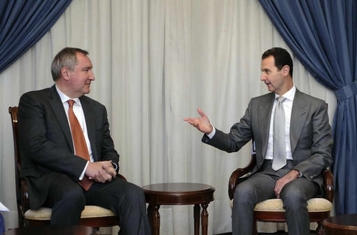 In this photo released by the Syrian official news agency SANA, Syrian President Bashar Assad, right, speaks with Russian Deputy Prime Minister Dmitry Rogozin in Damascus, Syria, Tuesday, Nov. 22, 2016. Russia has backed Assad with vast military support as he fights to put down an uprising that is approaching its sixth year. (SANA via AP)
