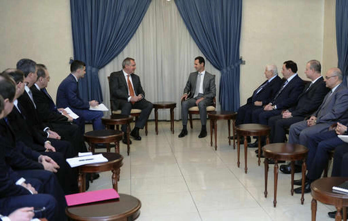 In this photo released by the Syrian official news agency SANA, Syrian President Bashar Assad, center right, meets with Russian Deputy Prime Minister Dmitry Rogozin, center left, in Damascus, Syria, Tuesday, Nov. 22, 2016. Russia has backed Assad with vast military support as he fights to put down an uprising that is approaching its sixth year. (SANA via AP)