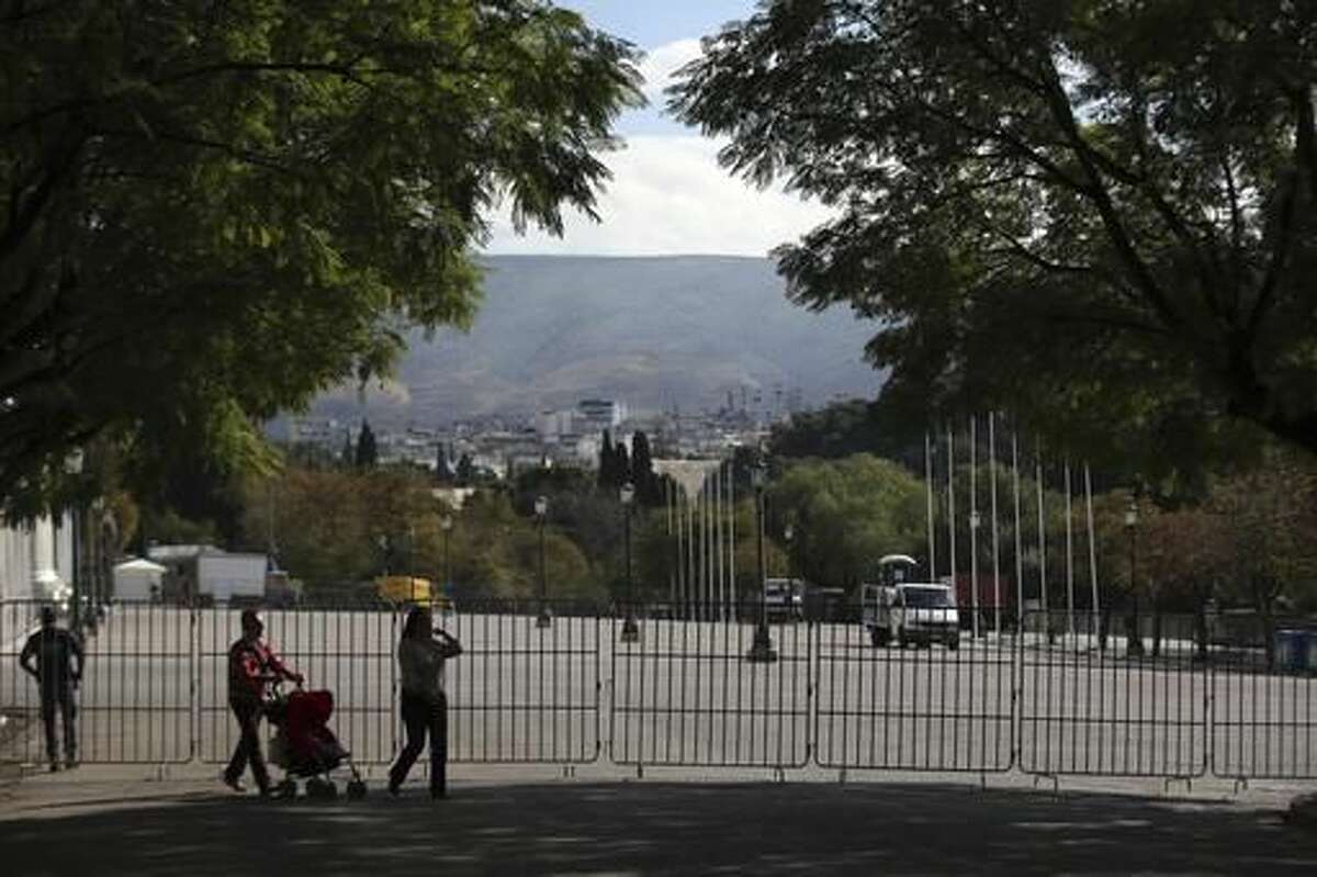 A couple pass by a fence outside Zappeio Conferenence Hall in Athens, Monday, Nov. 14, 2016. Thousands of police are to be deployed in Athens for draconian security measures during a two-day visit to Athens by President Barack Obama starting Tuesday. (AP Photo/Yorgos Karahalis)