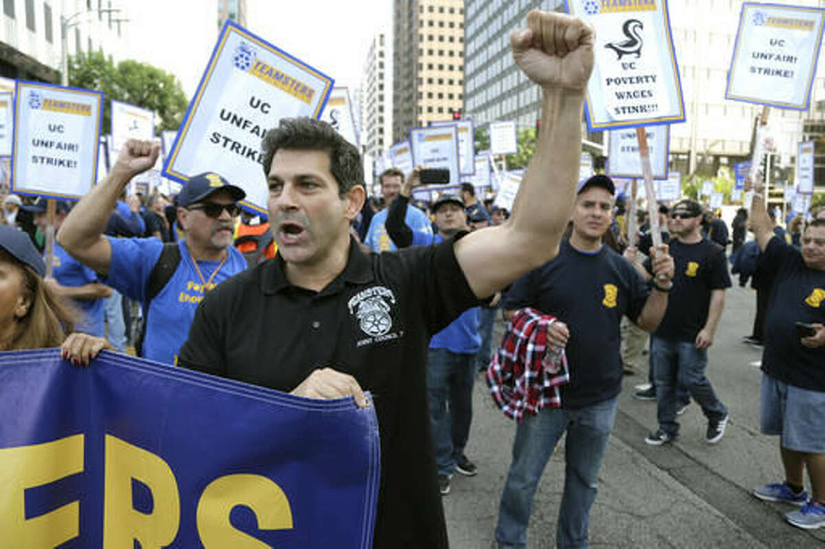 """Several hundred union members wearing Teamsters shirts and hats participate in a rally at the University of California Los Angeles carrying signs reading """"fair contract now!"""" and """"UC unfair!"""" Wednesday, Nov. 16, 2016, in Los Angeles. Electricians, elevator mechanics, plumbers and other workers at UCLA walked off the job Wednesday to demand higher wages in a daylong strike. No major disruptions were reported. (AP Photo/Nick Ut)"""
