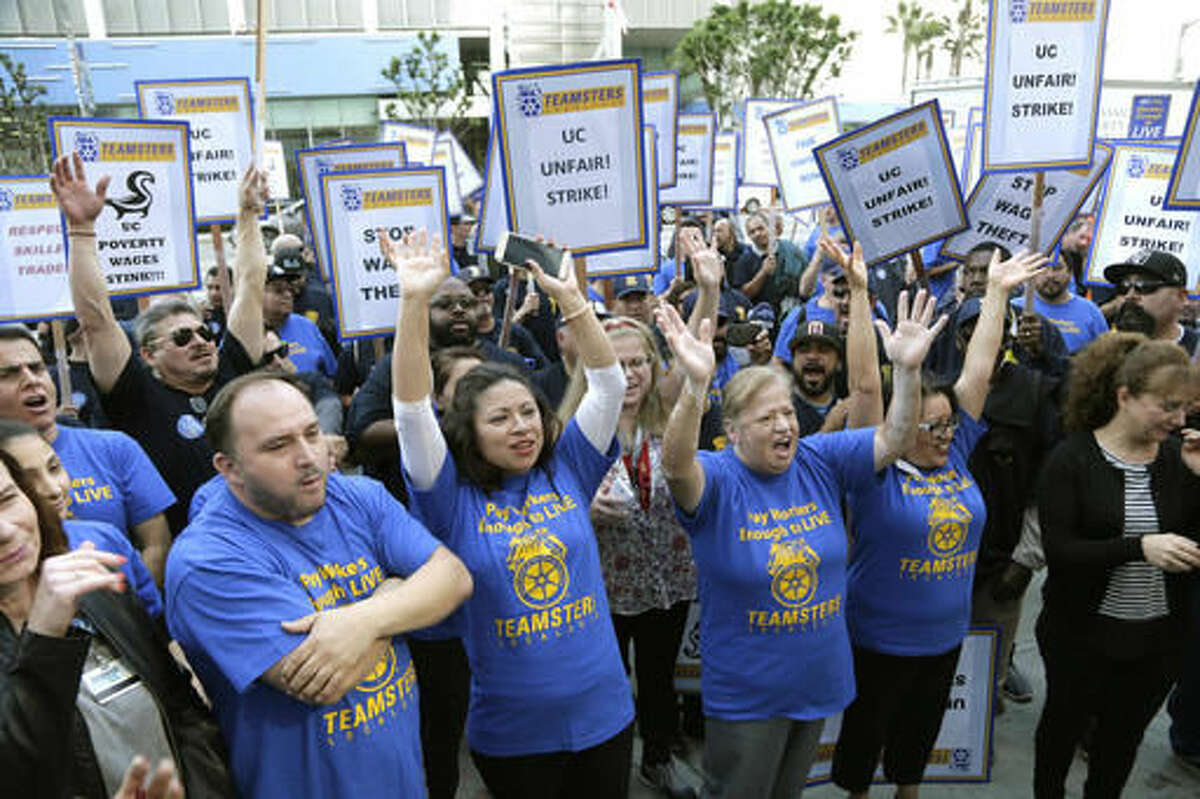 """Several hundred union members wearing Teamsters shirts participate in a rally at the University of California Los Angeles carrying signs reading """"fair contract now!"""" and """"UC unfair!"""" Wednesday, Nov. 16, 2016, in Los Angeles. Electricians, elevator mechanics, plumbers and other workers at UCLA walked off the job Wednesday to demand higher wages in a daylong strike. No major disruptions were reported. (AP Photo/Nick Ut)"""