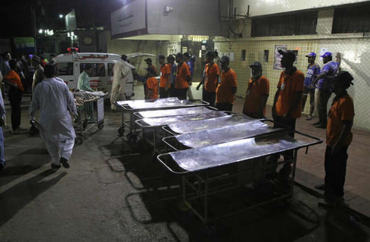 Staff members of a local hospital wait for casualties of bomb blast at a Sufi shrine, in Karachi, Pakistan, Saturday, Nov. 12, 2016. Pakistani police say a bomb blast at a Sufi shrine has killed several people and wounded many others in the country's southwest. Sarfaraz Bugti, home minister for Baluchistan province, confirmed that the blast occurred with hundreds in attendance at the shrine of Sufi saint Shah Bilal Noorani. (AP Photo/Fareed Khan)