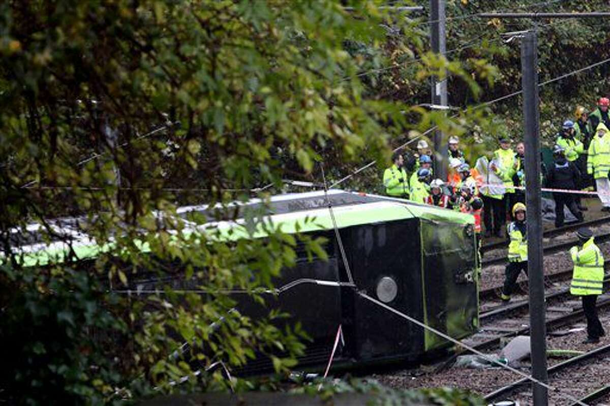 Emergency service workers attend the scene of a derailed tram in Croydon, south London, Wednesday Nov. 9, 2016. A tram derailed in London before dawn on Wednesday, leaving at least 50 people injured and several trapped, the emergency services said. (Steve Parsons/PA via AP)