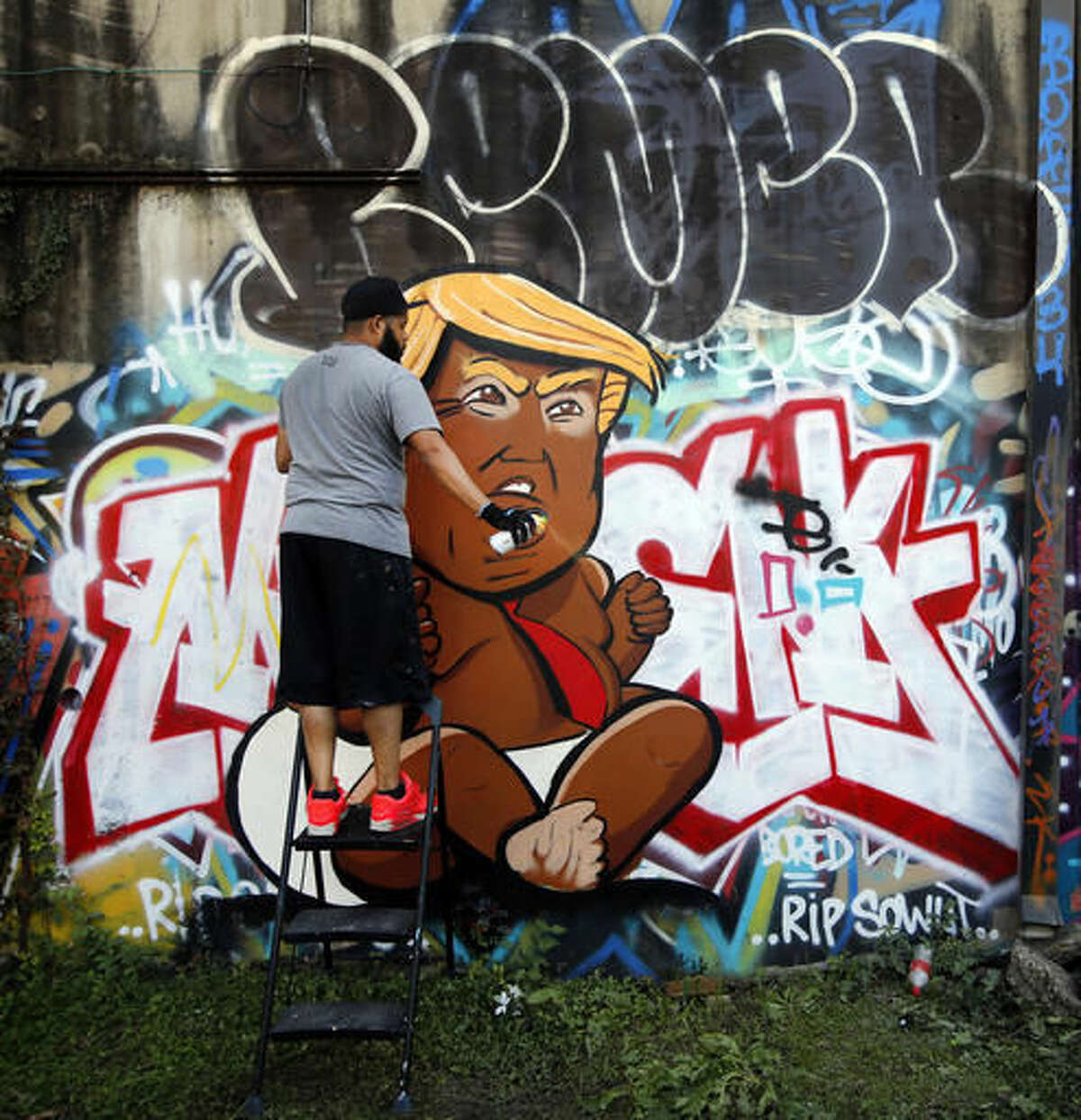 In a Saturday, Nov. 12, 2016 photo, Dallas artist Jeremy Biggers clears his spray can as he paints a caricature of President-elect Donald Trump during GO PAINT DAY at the Fabrication Yard in Dallas. This is only the third time the realism painter has created artwork with a spray can. The two days are dedicated to celebrating hip hop history month with paint, music, dancing and community. (Tom Fox/The Dallas Morning News via AP)