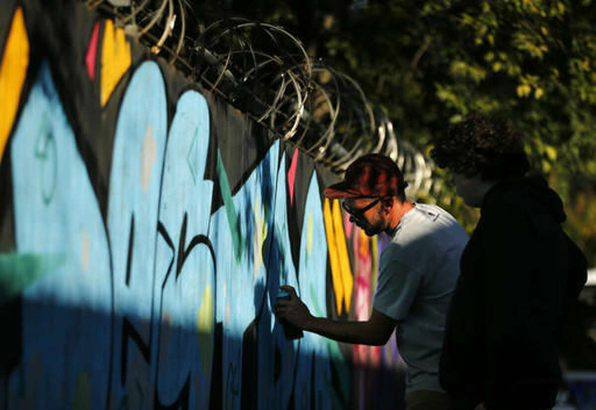 In a Saturday, Nov. 12, 2016 photo, an artist who gave his name as TR, creates spray art on a wooden fence at the Fabrication Yard in Dallas during GO PAINT DAY. The two days are dedicated to celebrating hip hop history month with paint, music, dancing and community. (Tom Fox/The Dallas Morning News via AP)