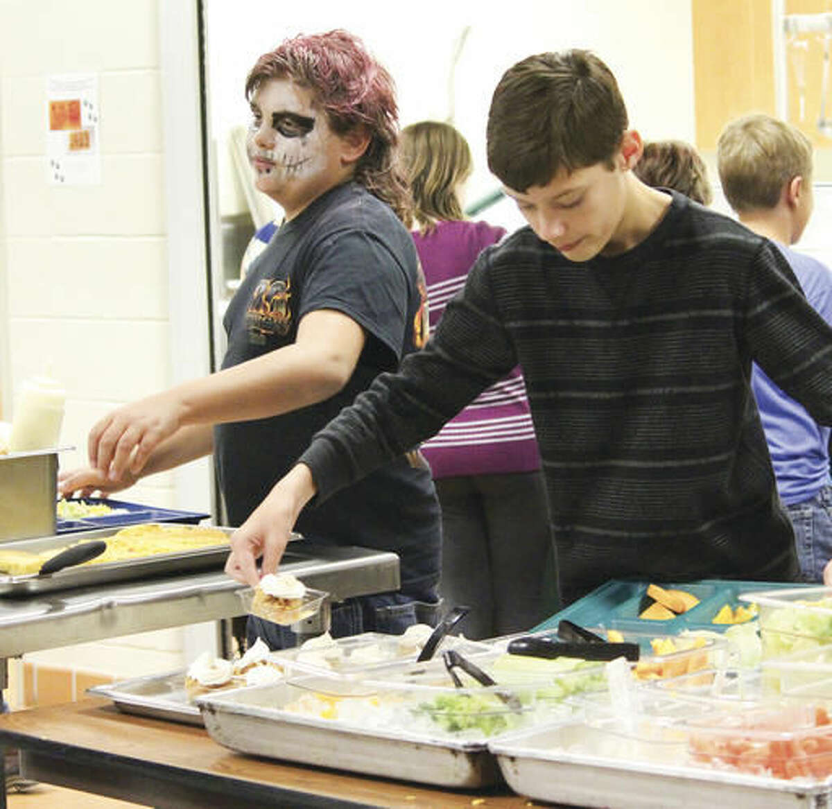 Brandon Rice, right, picks up an apple crisp from the Thermopolis Middle School lunch room. The apple crisp was made from apples picked by students in the farm to school program and served on Halloween. (Tesia Galvan/Northern Wyoming Daily News via aP)