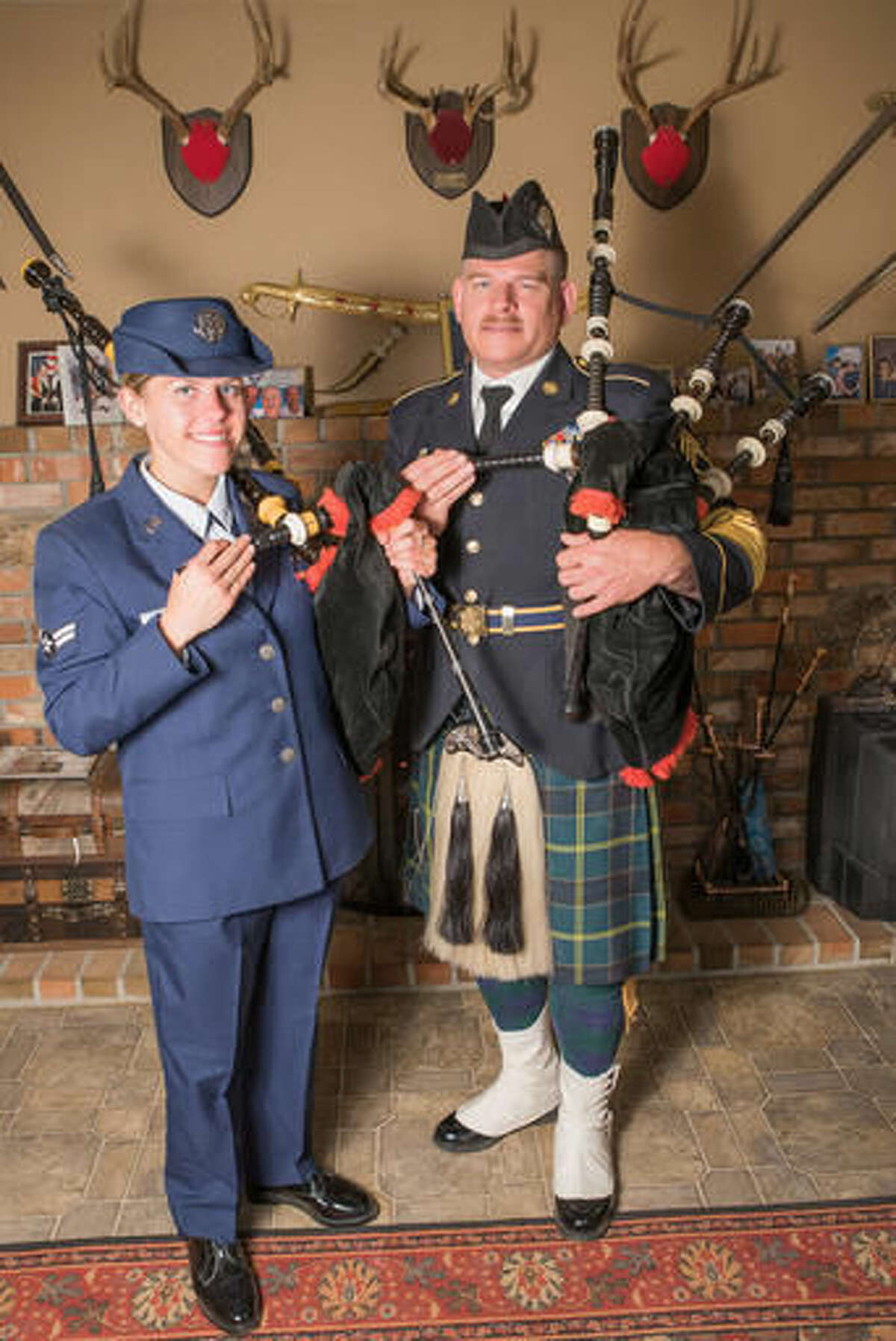 In this Nov. 7, 2016 photo, Air Guard Senior Airman Mariah Connell and her father, Sgt. 1st Class Michael Connell pose for a photo in a living room holding their military bagpipes in Reno, Nev. Michael Connell served for the Nevada Air National Guard, and now he serves in the U.S. Army. Connell, the only military bagpiper in Nevada, will retire by the end of this year, reported the Reno Gazette-Journal. After he retires, his daughter, Mariah Connell, 23, will take over as the only military piper in Nevada. (Mike Higdon/The Reno Gazette-Journal via AP)