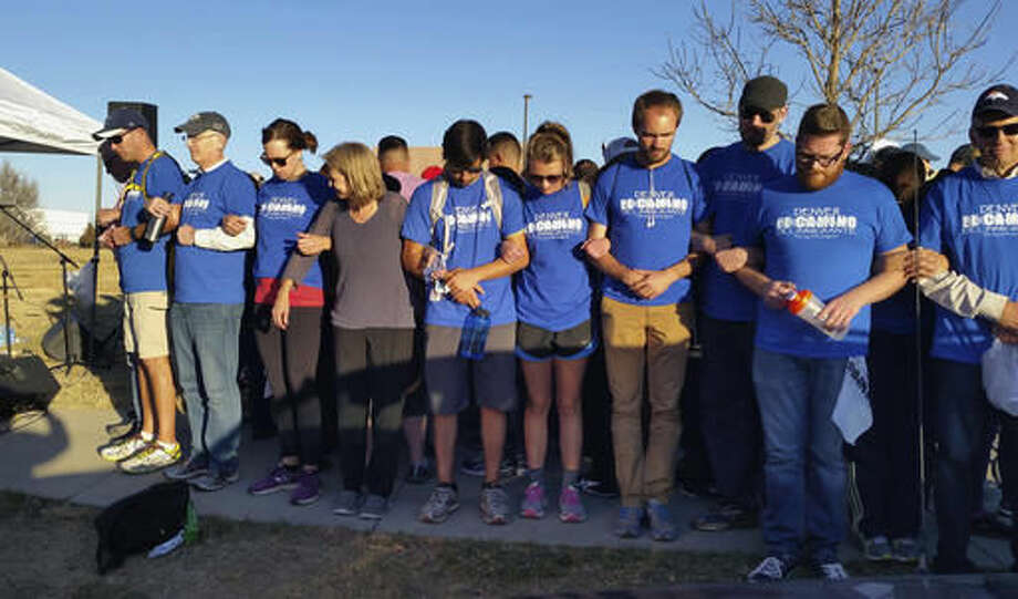 """In this Saturday, Nov. 12, 2016, photo, supporters link arms around a group of Hispanic demonstrators at the Immigration and Customs Enforcement detention center in Aurora, Colo., after an 11-mile prayer walk to show solidarity with immigrants. Several hundred people marched from Denver to Aurora on Saturday to urge the new Trump administration and Congress to work together to solve problems with immigration, saying they """"want to build bridges, not walls."""" (AP Photo/Steven K. Paulson) Photo: Steven K. Paulson"""