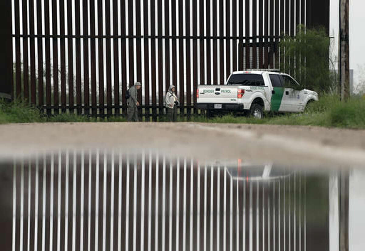 In this Sunday, Nov. 13, 2016, photo, a U.S. Customs and Border Patrol agent passes birdwatchers Rayborn and Nancy Hill along a section of border wall in Hidalgo, Texas. The idea of a concrete wall spanning the entire 1,954-mile southwest frontier collides head-on with multiple realities, like a looping Rio Grande, fierce local resistance, and cost. (AP Photo/Eric Gay)