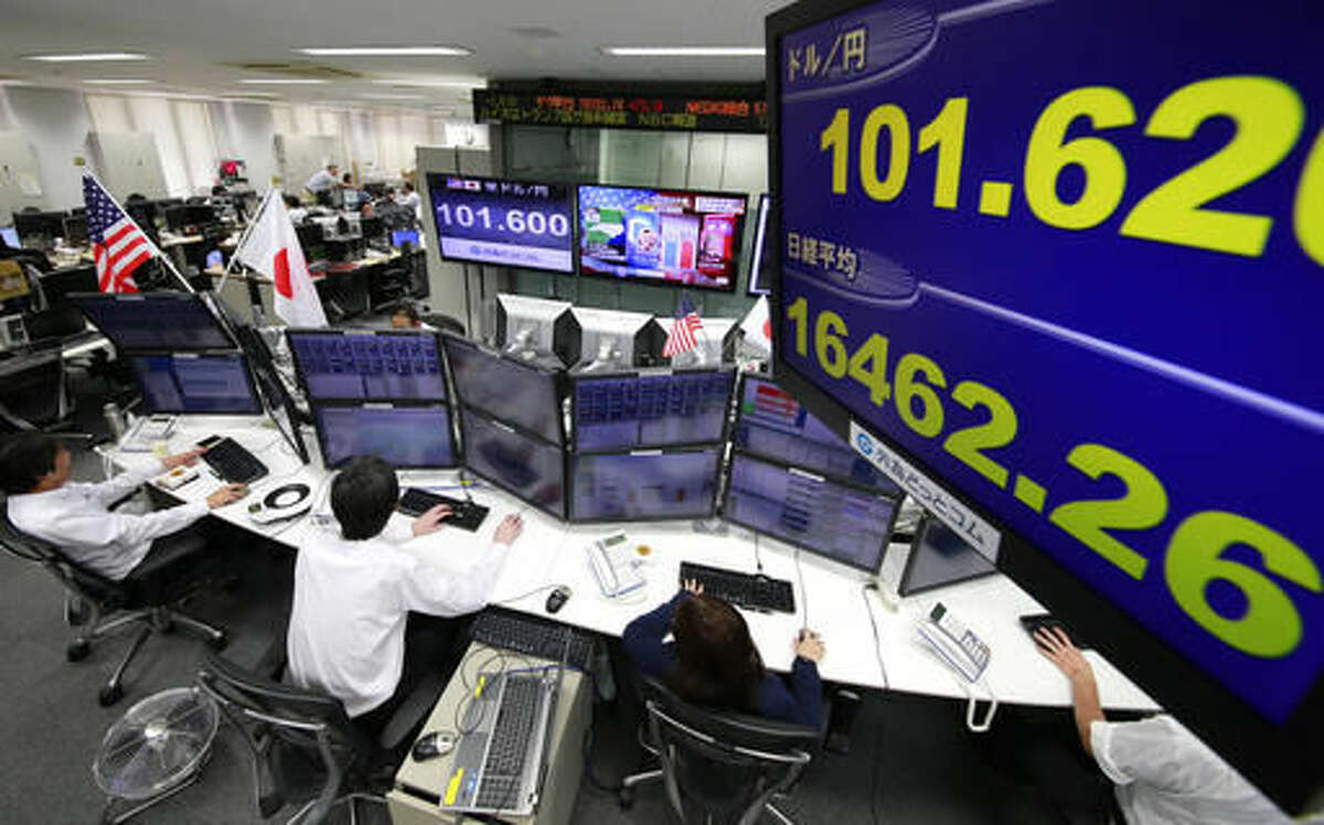 Money traders watch computer screens with the day's exchange rate between yen and the U.S. dollar at a foreign exchange brokerage in Tokyo, Wednesday, Nov. 9, 2016. Asian shares have shed early gains, tumbling Wednesday as Donald Trump gained the lead in the electoral vote count in the presidential election. Dow and S&P futures also plunged. Earlier, investors had appeared persuaded that Hillary Clinton, seen as a more stable choice, would prevail.(AP Photo/Shizuo Kambayashi)