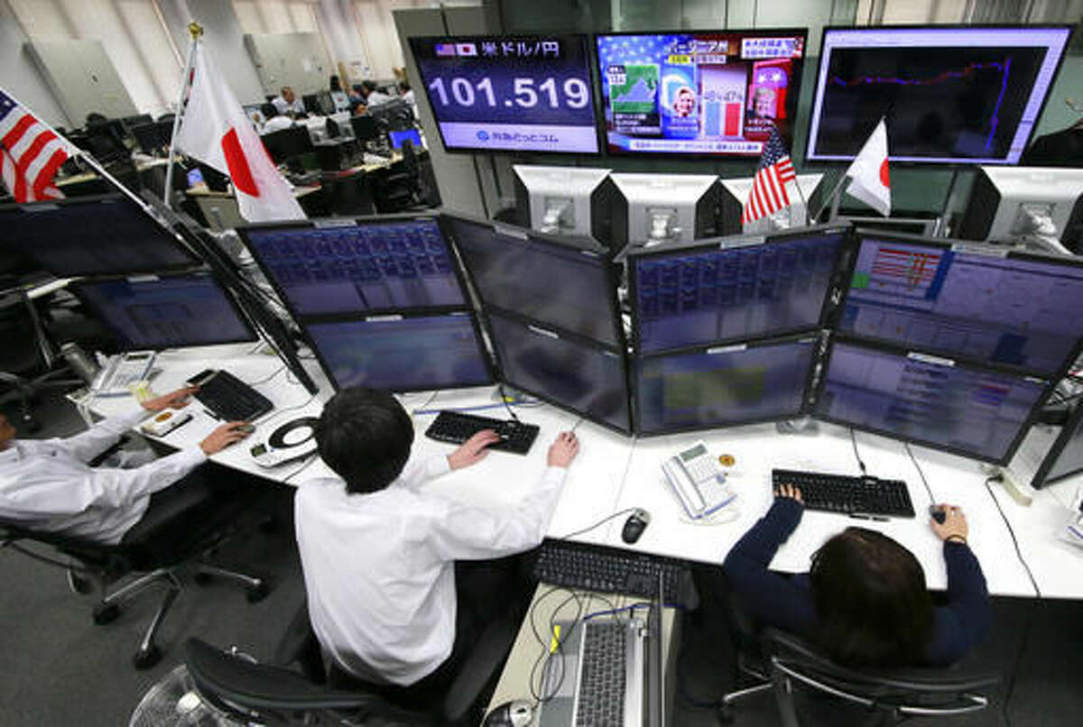 Money traders watch computer screens with the day's exchange rate between yen and the U.S. dollar at a foreign exchange brokerage in Tokyo, Wednesday, Nov. 9, 2016. Asian shares have shed early gains, tumbling Wednesday as Donald Trump gained the lead in the electoral vote count in the presidential election. Dow and S&P futures also plunged. Earlier, investors had appeared persuaded that Hillary Clinton, seen as a more stable choice, would prevail. (AP Photo/Shizuo Kambayashi)