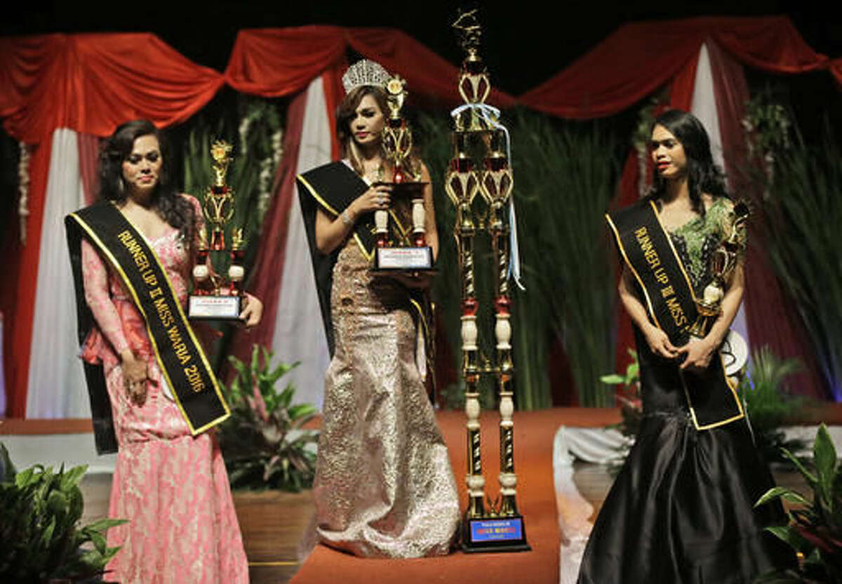 In this Friday, Nov. 11, 2016, photo, Qienabh Tappii, center, holds her trophy as she stands on the stage with first runner up Sefty Castanyo, left, and third place winner Amanda Sandova, right, after winning the Miss Transgender Indonesia pageant in Jakarta, Indonesia. Opposition from Islamic hardliner groups prevented the long-running event twice in recent years as Indonesia's police often look the other way when they attack or intimidate LGBT groups. (AP Photo/Dita Alangkara)