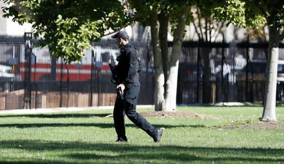A U.S. Secret Service officer walks the grounds near the North Portico during a lock-down at the White House, Saturday, Nov. 5, 2016 in Washington. According to the Secret Service, a Secret Service Uniformed Division Officer noticed a man with a weapon in a holster while walking on Pennsylvania Avenue near Madison Place. The officer confronted the man and a brief struggle ensued, before the man was arrested. President Obama was not at the White House during the incident. (AP Photo/Alex Brandon) Photo: Alex Brandon