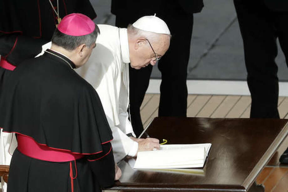 Pope Francis signs a letter at the end of a Mass on the occasion of the closing of the Holy Door of St. Peter's Basilica at the Vatican, Sunday, Nov. 20, 2016. The Vatican said the letter, addressed to all the church, expressed the pope's intention that the church can continue to live out the mercy with the same intensity felt during the entire special Jubilee Holy Year. (AP Photo/Gregorio Borgia) Photo: Gregorio Borgia