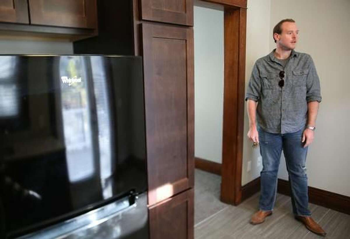 In this Nov. 11, 2016 photo, Brandon Johnsen walks through a Bradford Rowhomes in Omaha, Neb. The property used a state historical tax credit to improve the apartments. (Megan Smith/Omaha World-Herald via AP)