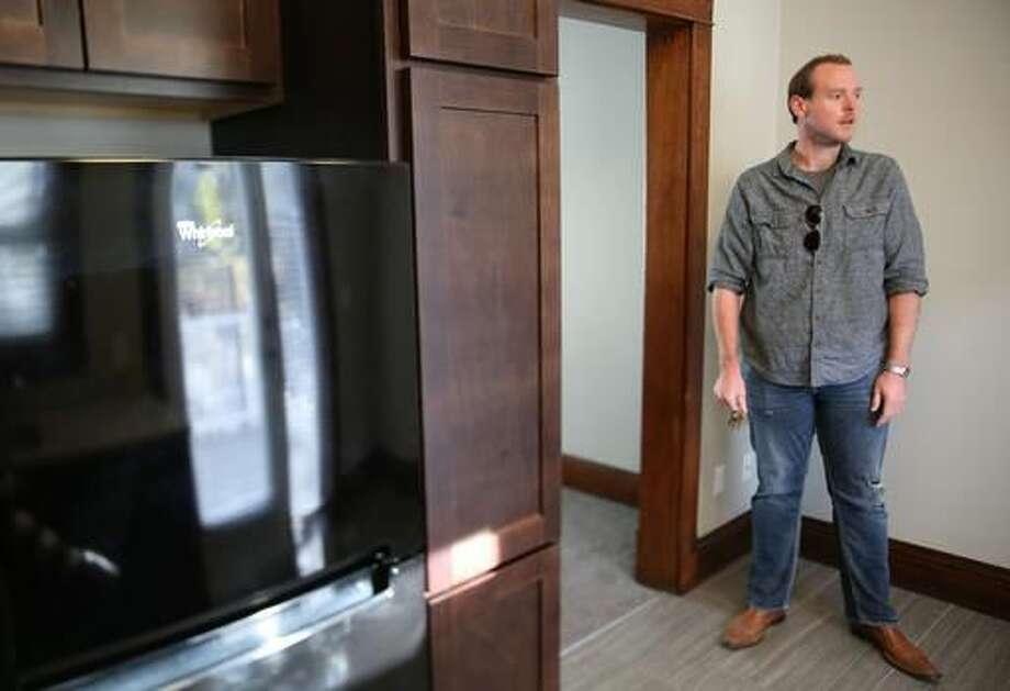 In this Nov. 11, 2016 photo, Brandon Johnsen walks through a Bradford Rowhomes in Omaha, Neb. The property used a state historical tax credit to improve the apartments. (Megan Smith/Omaha World-Herald via AP) Photo: Megan Smith