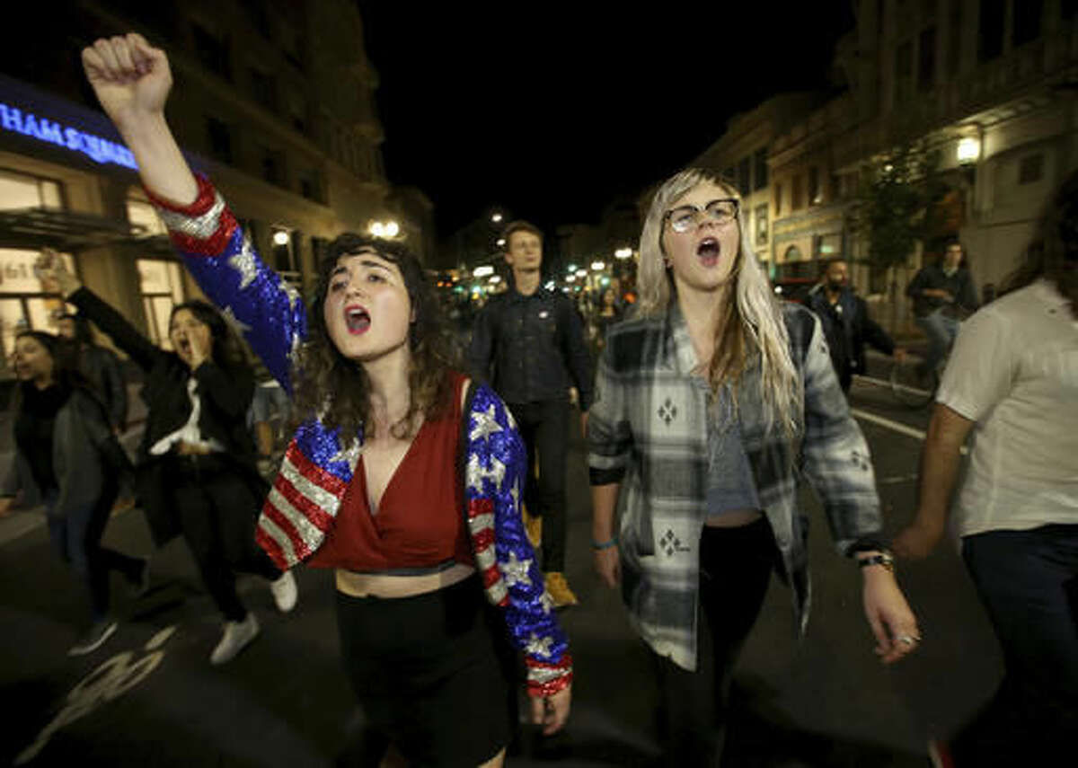 Madeline Lopes, left, and Cassidy Irwin, both of Oakland, march with other protesters in downtown Oakland, Calif., early Wednesday, Nov. 9, 2016. President-elect Donald Trump's victory set off multiple protests. (Jane Tyska/Bay Area News Group via AP)