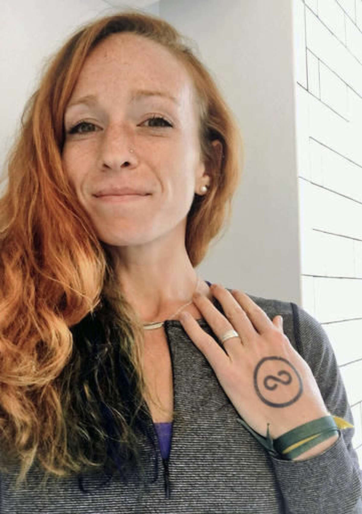 In this Nov. 2, 2016, self-portrait provided by Esther Atkins, the elite marathoner displays a temporary tattoo of the Clean Sport Collective in Greenville, S.C. The new anti-doping initiative, launched earlier this month by U.S. athletes and fitness companies through a social media campaign, promotes drug-free and transparent training and competition. Participating athletes publicly pledge to live, train and compete