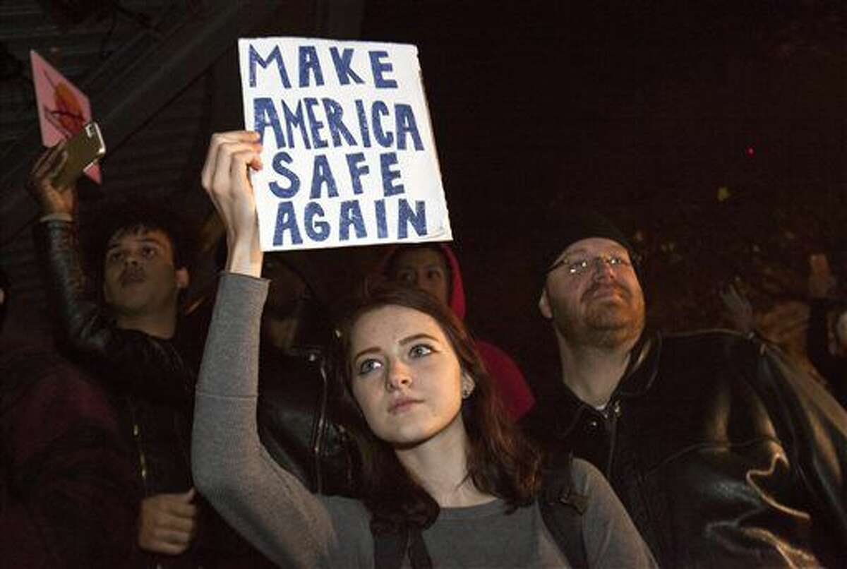 Protesters gather at Rosa Parks Circle in Grand Rapids, Mich., Thursday, Nov. 10, 2016, in opposition of Donald Trump's presidential election victory. (Cory Morse/The Grand Rapids Press via AP)