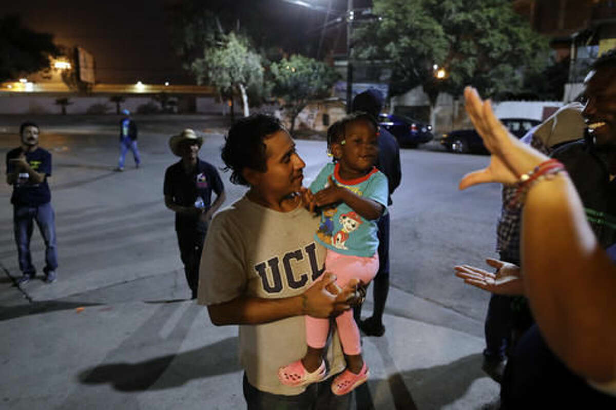 FILE - In this Nov. 14, 2016 file photo, Guatamalan Elvin Vazquez, center, holds a Haitian girl migrating with her family, at a migrant shelter in Tijuana, Mexico. A surge in border crossings and a lack of immigration jail space have prompted the federal government to start releasing Haitian immigrants who have been entering the country in large numbers in recent months, backtracking on a pledge to jail the migrants. A U.S. government official said the decision to free Haitians arriving in Arizona and California is in response to a lack of jail space. Thousands of Haitians have arrived at the U.S. border with Mexico in recent months, many after traveling 7,000 miles by foot, taxi and bus. (AP Photo/Gregory Bull, File)
