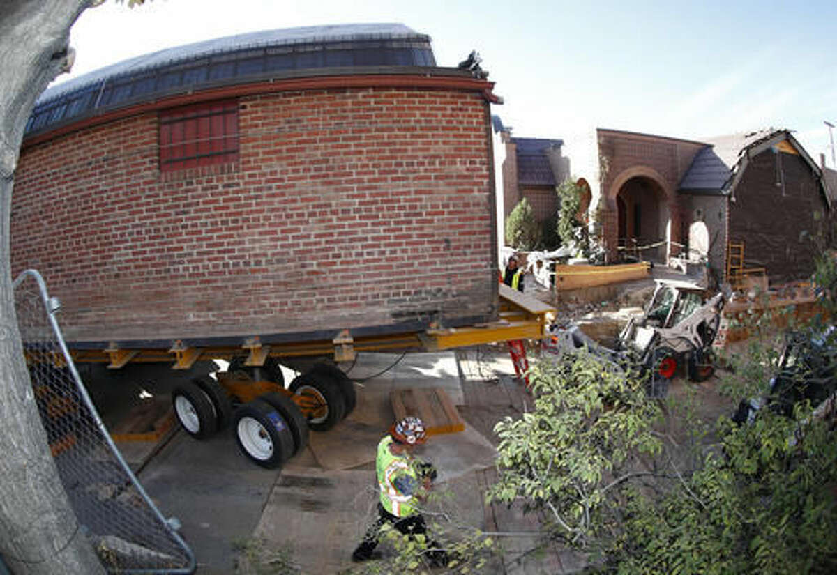 Workers prepare to move the building that housed the studio of renowned artist Vance Kirkland from its location east of the State Capitol building to a new location near the art museum early Sunday, Nov. 6, 2016, in Denver. The move, which will take the entire day to complete, will be carried out by using remote-controlled wheels to propel the structure eight blocks through the center of the city. (AP Photo/David Zalubowski)