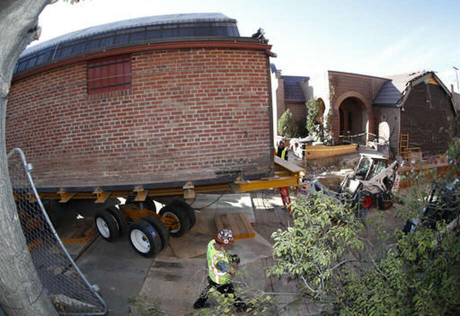 Workers prepare to move the building that housed the studio of renowned artist Vance Kirkland from its location east of the State Capitol building to a new location near the art museum early Sunday, Nov. 6, 2016, in Denver. The move, which will take the entire day to complete, will be carried out by using remote-controlled wheels to propel the structure eight blocks through the center of the city. (AP Photo/David Zalubowski) Photo: David Zalubowski