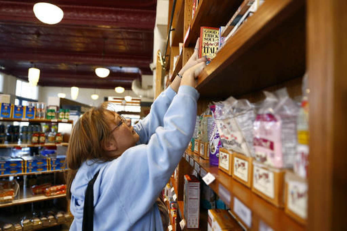 ADVANCE FOR SATURDAY, NOV. 19, 2016 - In this Oct. 27, 2016 photo, Marcy Martinez, who came to The Farmer's Pantry for the first time, looks for a cookbook for a recipe for an Italian soup, in Greeley, Colo. Martinez said she plans to come back again to find recipes for future meals. (Alyson McClaran /The Greeley Tribune via AP)