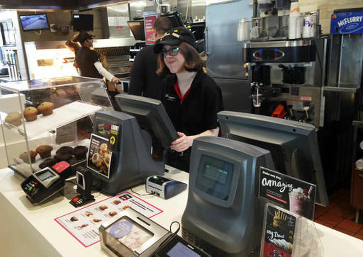 In this Oct. 6, 2016 photo, Lauren Curtis waits on a customer at the front counter of a McDonald's in Potterville, Mich. Curtis, 18, and her four siblings are non-identical quintuplets, all of whom work at the Lansing-area restaurant. (AP Photo/Mike Householder)
