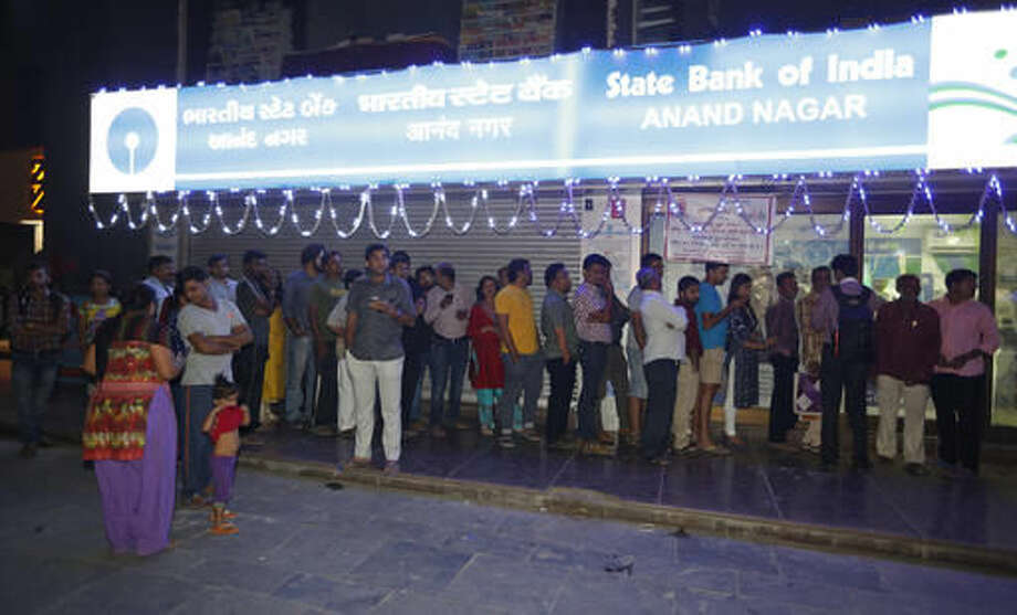 Indians stand in a queue in front of an ATM machine in Ahmadabad, India, Tuesday, Nov. 8, 2016. India's highest-denomination currency notes are being withdrawn immediately from circulation, the country's prime minister said Tuesday night, a surprise announcement designed to fight corruption and target people who have stashed away immense amounts of cash. Across the country Tuesday night, people rushed to bank ATM machines where money could be withdrawn in 100-rupee notes, trying to avoid being caught without cash over the next few days. (AP Photo/Ajit Solanki) Photo: Ajit Solanki