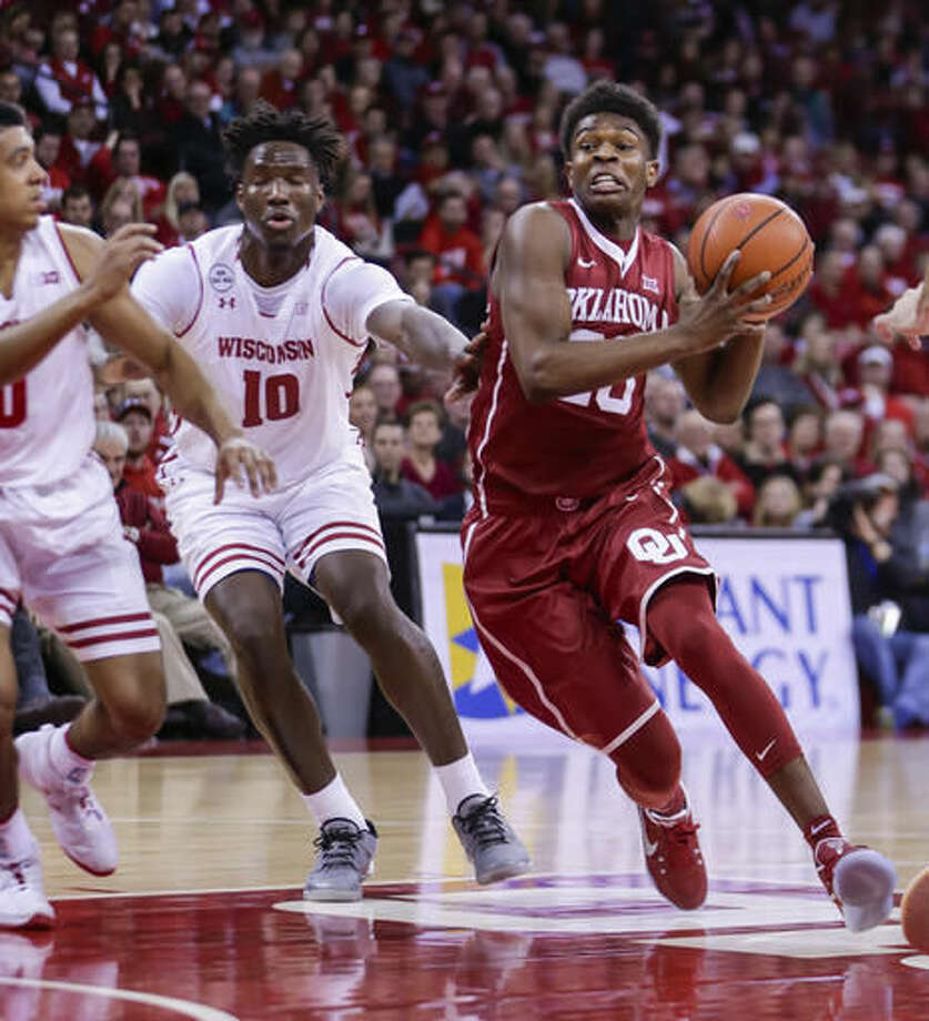 Oklahoma's Kameron McGusty (20) drives past Wisconsin's Nigel Hayes (10) during the first half of an NCAA college basketball game Saturday, Dec. 3, 2016, in Madison, Wis. (AP Photo/Andy Manis)