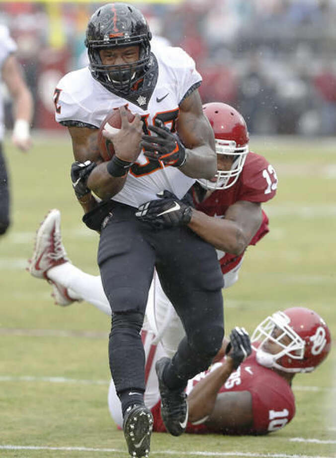 Oklahoma State running back Chris Carson (32) is tackled from behind by Oklahoma safety Ahmad Thomas (13) during the first half of an NCAA college football game, Saturday, Dec. 3, 2016, in Norman, Okla. (AP Photo/Alonzo Adams)