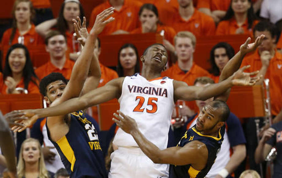 Virginia forward Mamadi Diakite (25) reacts to a foul as West Virginia forward Esa Ahmad (23), left, and West Virginia guard Jevon Carter, right, defend during the first half of an NCAA college basketball game in Charlottesville, Va., Saturday, Dec. 3, 2016. (AP Photo/Steve Helber)